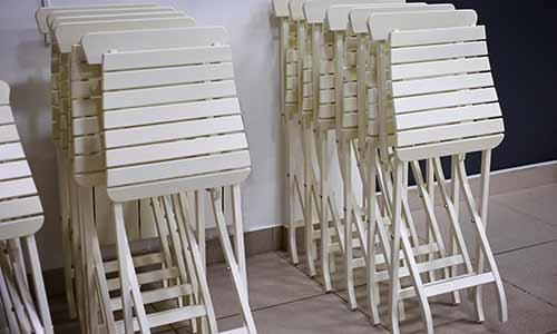 Stacks of white folding chairs leaning on a wall, waiting for a better storage solution